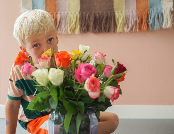 jongen ruikt aan rozen