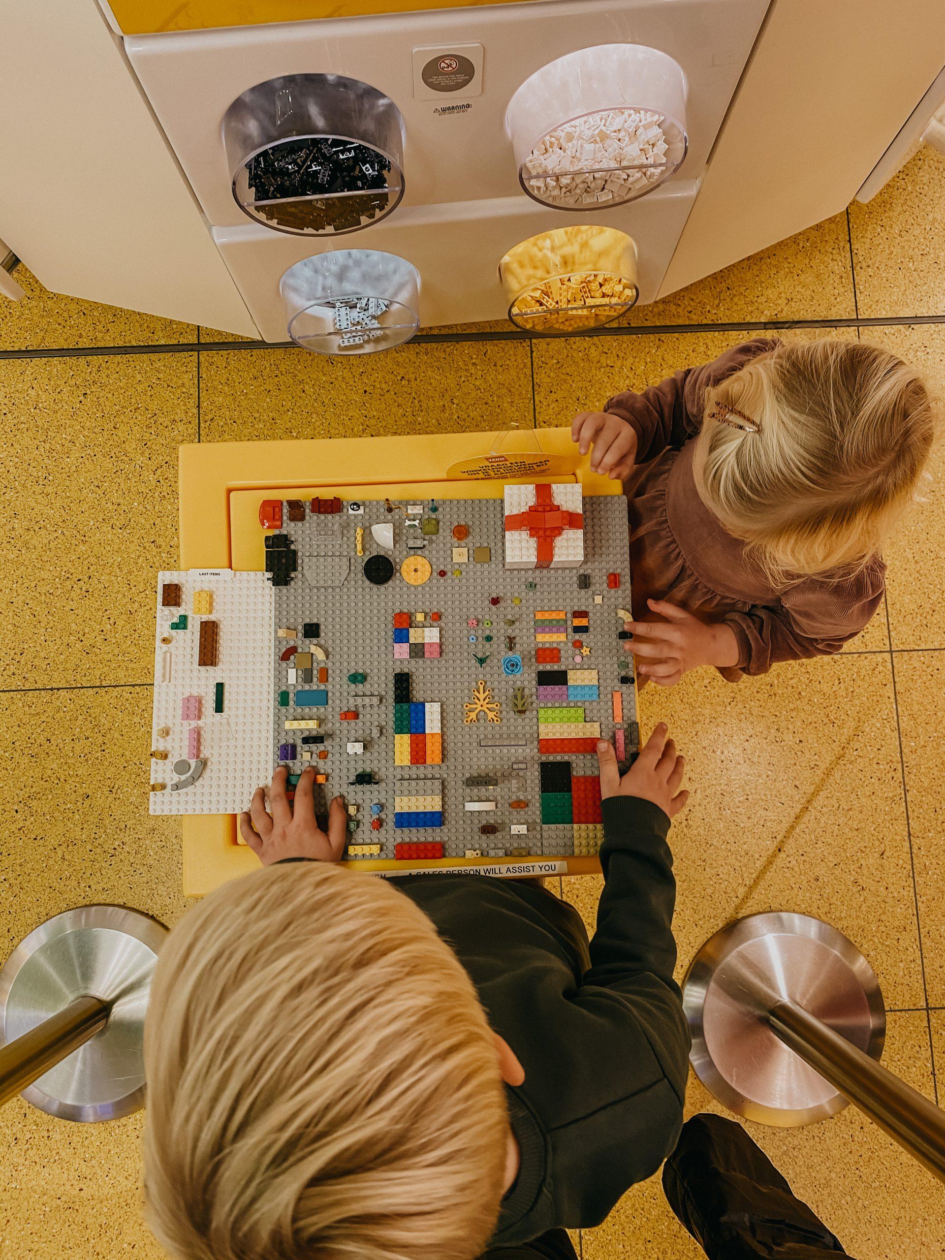 Samen een emmertje steentjes vullen bij de Pick-a-Brick wall in de LEGO Store Amsterdam